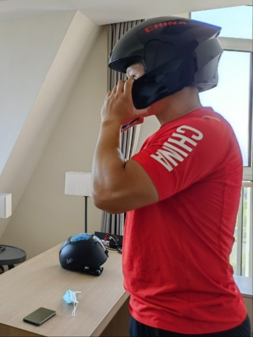 An athlete trying on his helmet